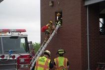 Firefighters train with mannequn on extension latter