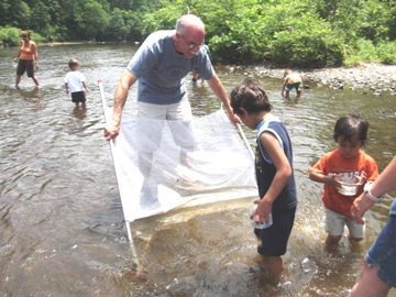 Program leader and children in creek